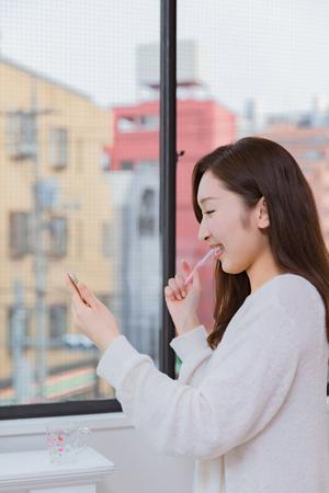 oral communication: Ladyn looking at mobile smartphone brushing teeth