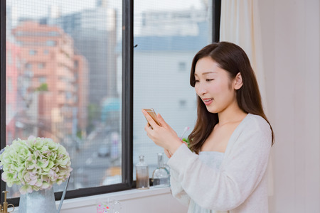 oral communication: Lady looking at mobile smartphone brushing teeth