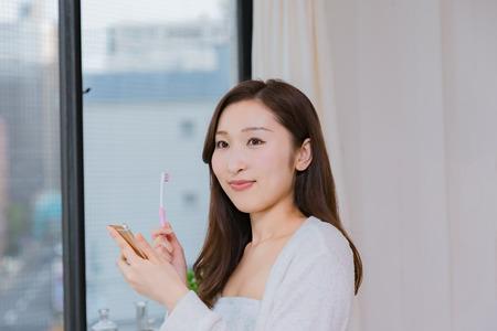 comunicacion oral: Señora que mira dientes móviles de teléfonos inteligentes cepillado