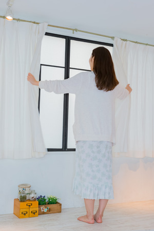 nightwear: Lady in nightwear opening curtain