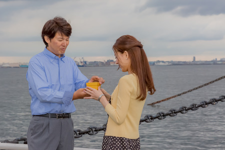 wharf: Business man giving present to lady at wharf