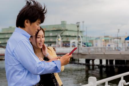 wharf: Couple using smart phone at wharf
