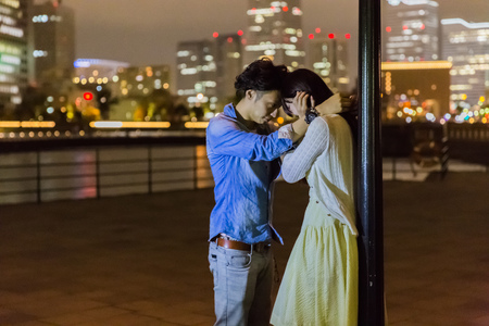 each: Couple touching forehead each other at wharf