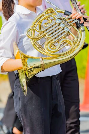student playing french horn, music instrucment