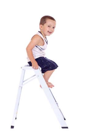 Cute little boy climbing on a stepladder Stock Photo