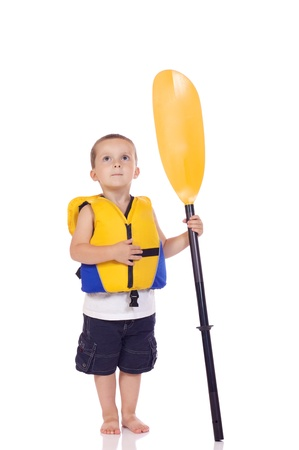 Cute little boy with a life jacket and a paddle