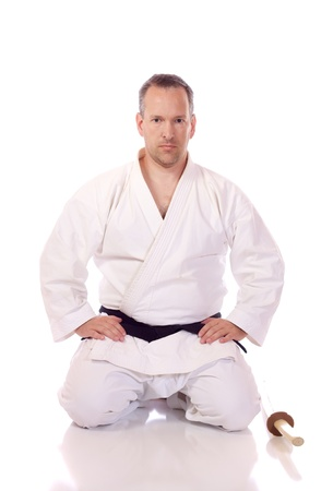 Man in karate-gi holding a boken in the seiza position