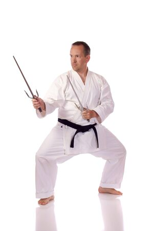 Man in karate-gi holding a pair of sai photo