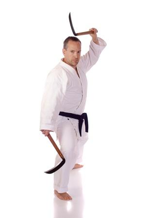 Man in karate-gi holding a pair of kama Imagens