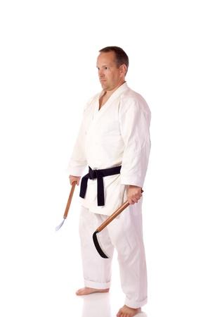 kama: Man in karate-gi holding a pair of kama Stock Photo