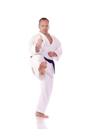 Man in karate-gi doing a front kick photo