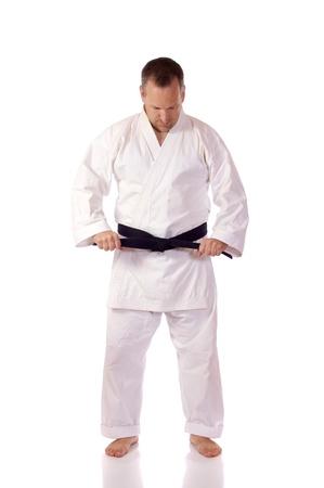 Man in karate-gi fastening his black belt Stock Photo