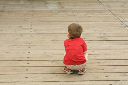 Little boy alone and crouched on a wooden sidewalk Stock Photo