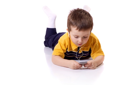 Cute little boy listening to music on a MP3 player Stock Photo