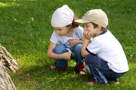burrow: Boy and girl looking at a burrow under a tree Stock Photo