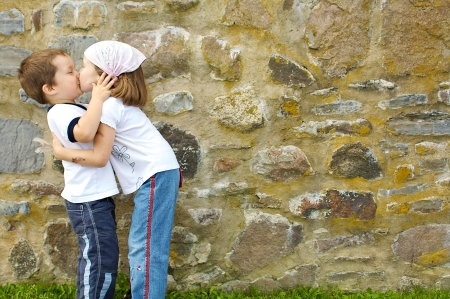 Little boy and girl kissing in front of a stone wall photo