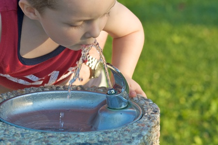 Small boy drinking from a fountain
