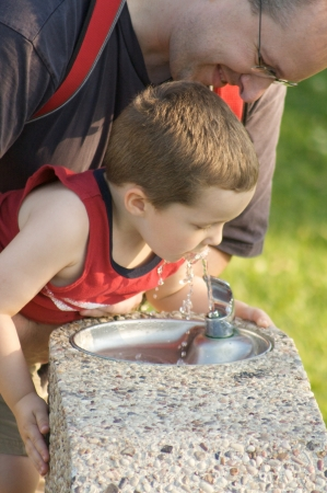 Father helping his son to drink from a fountain Stock Photo