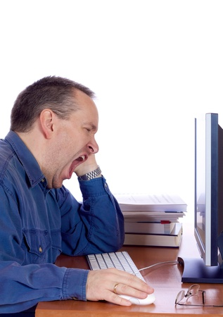 Tired man yawning at his computer keyboard Stock Photo
