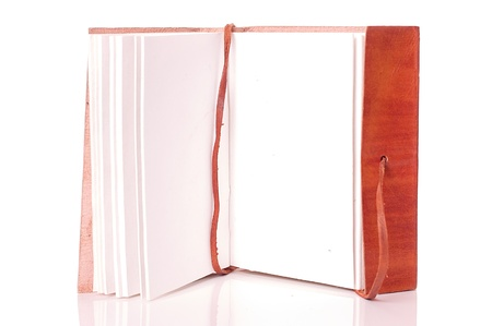 Old leather-bound book with parchment paper inside on a white background