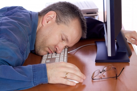 Man asleep on his computer keyboard Stock Photo