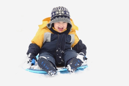 Little boy sliding in the snow photo