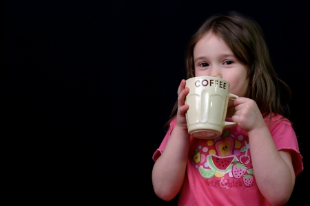 Little girl holding a cup of coffee