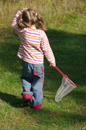Little girl hunting butterflies with a net in a trail in the woods