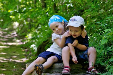 Brother and sister sitting on a rock in a beautiful trail in the woods photo