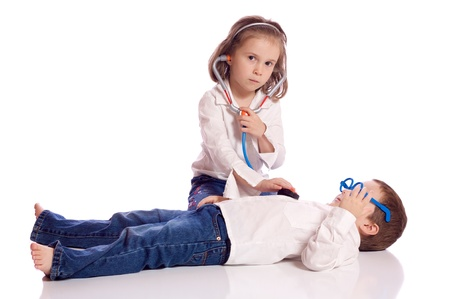 Cute little brother and sister playing doctor photo