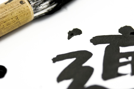 Black chinesejapanese symbol with a calligraphy brush resting nearby. This is a close macro shot with very low depth of field. The japanese form is pronounced DO and means The Way. Stock Photo