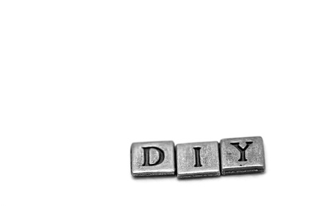 yourself: Metal scrapbooking letters spelling DIY: Do It Yourself. They lay on a white background. Stock Photo