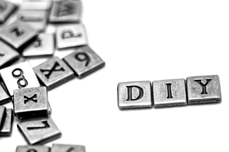 avocation: Metal scrapbooking letters spelling DIY: Do It Yourself. They lay on a white background and there is a bunch of other letters laying by. Stock Photo