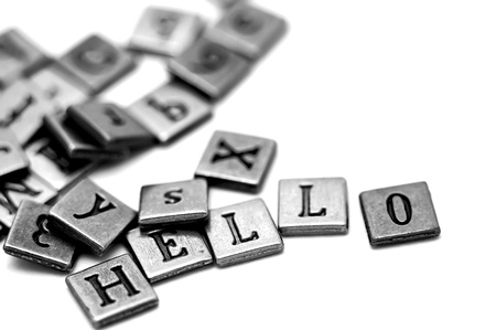 Metal scrapbooking letters spelling Hello. They lay on a white background and there is a bunch of other letters laying by. Stock Photo - 18483092