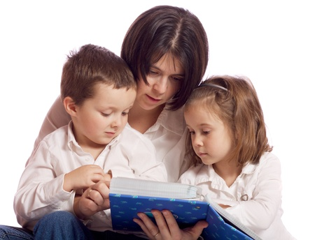 Mother, daughter and son looking at a photo album Imagens