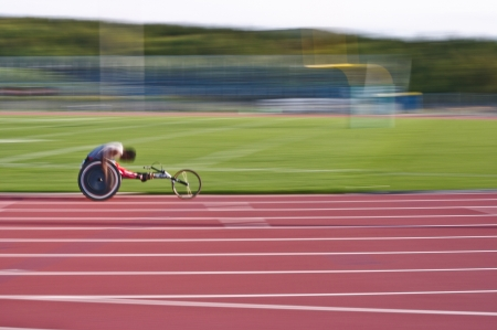 Black athlete racing in a wheelchair on a track