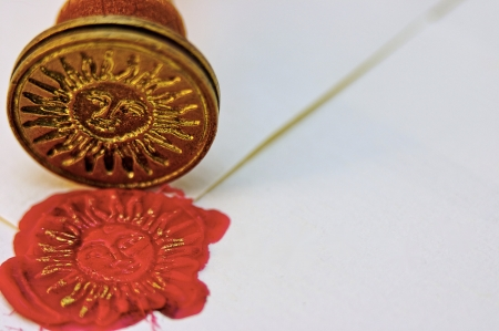 Signet stamped in red wax and gold ink to seal a parchment envelope Stock Photo - 18484948