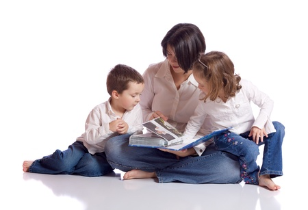 Mother, daughter and son looking at a photo album Stock Photo