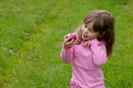 Little girl dressed in pink and picking apples in an appletree Stock Photo - 18484517