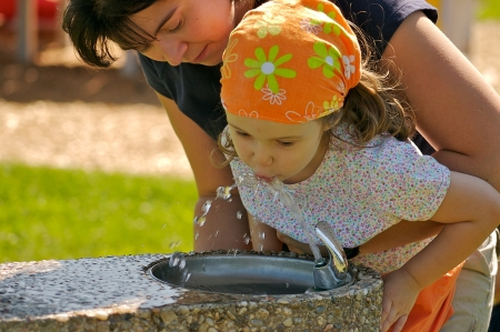 Mother helping her daughter to drink from a fountain