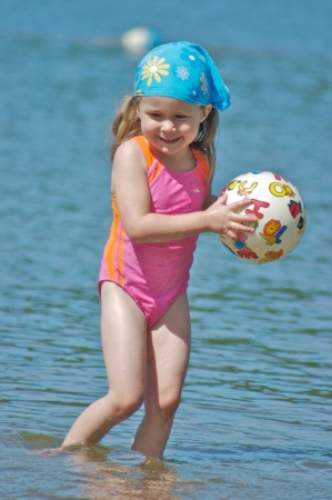 river: Cute little girl playing with a ball in the water