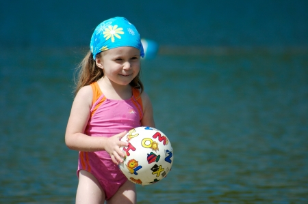 Cute little girl playing with a ball in the water