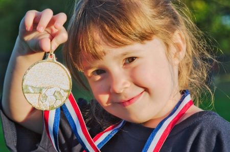 Little girl holding a gold medal with a soccer pattern at sunset