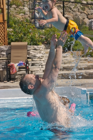 grasp: Father and son playing in the pool Stock Photo