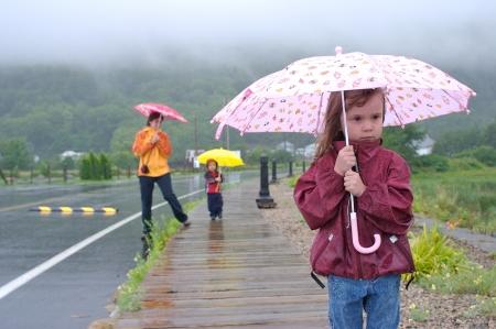 UOMO pioggia: Madre di famiglia, la figlia e il figlio a piedi e giocare sotto la pioggia con gli ombrelli colorati