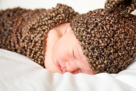 Newborn baby boy resting in a wool cocoon photo