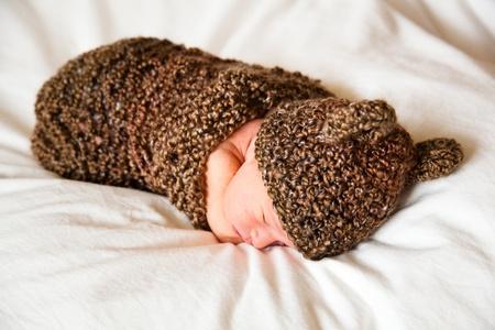 Newborn baby boy resting in a wool cocoon