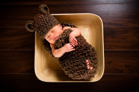 Newborn baby boy resting in a wool cocoon in a plate on a wooden floor