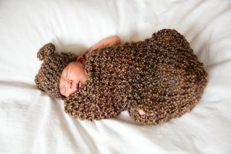 Newborn baby boy resting in a wool cocoon photo