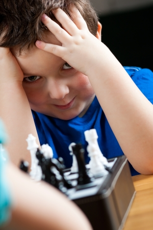 Cute little boy playing chess photo
